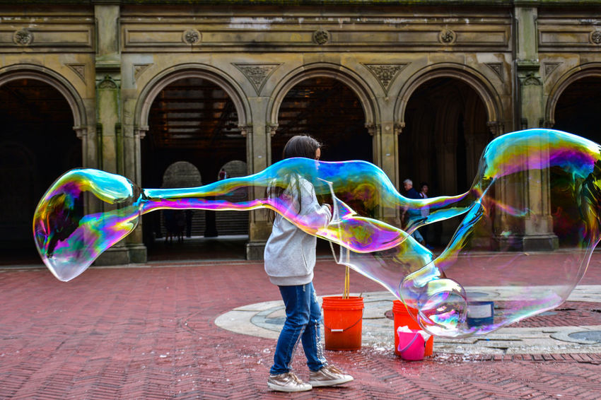 Arch Architecture Blowing Bubble Bubble Wand Building Exterior Built Structure Casual Clothing Day Double Rainbow Fragility Full Length Fun Holding Leisure Activity Lifestyles Multi Colored One Person Outdoors People Rainbow Real People Soap Sud Spectrum Standing