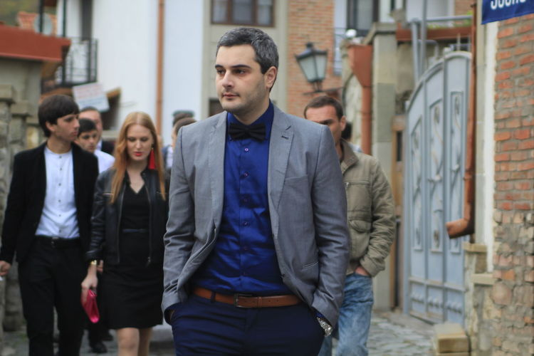 Businessman with hands in pockets walking on street