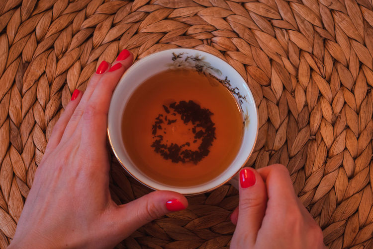 Hands holding a cup of red tea