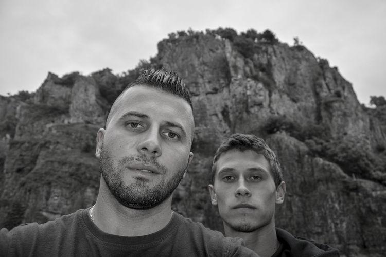 Portrait of men against rock formation