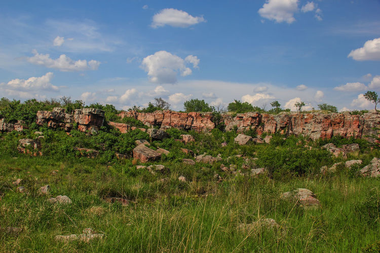 Rock formation on grassy field against sky at pipestone national monument