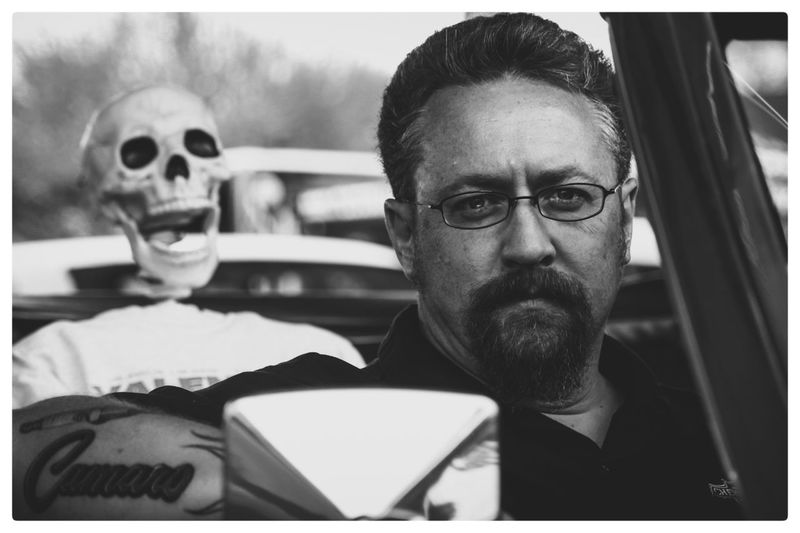 Portrait of mature man against skull in car during halloween