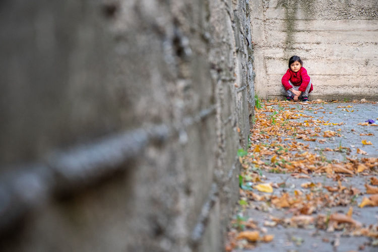 Girl crouching on land against wall