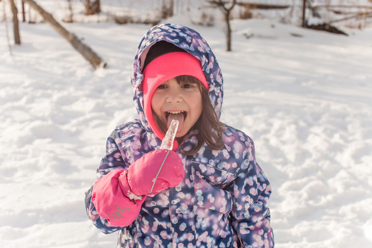 Smiling girl standing on snow during winter