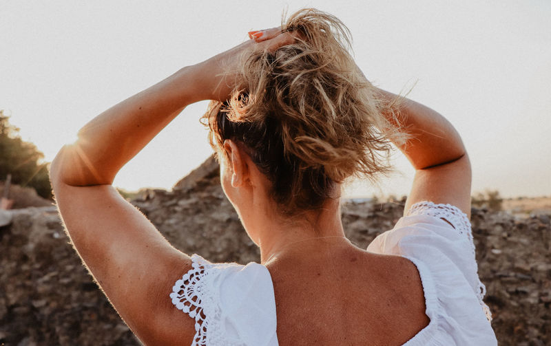 Rear view of mature woman tying hair while standing at beach against sky