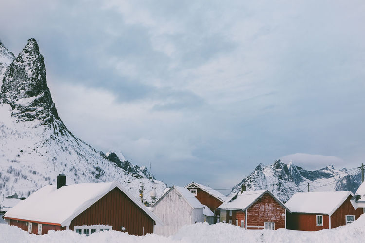 Houses by snow covered mountains against sky
