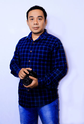 Portrait young Asian Photographer Looking At Camera One Person Portrait Three Quarter Length Standing Front View Studio Shot Young Adult Indoors  Smiling Casual Clothing White Background Young Men Technology Holding Clothing Wall - Building Feature Leisure Activity