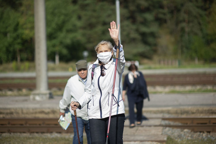 A group of senior travelers with masks on their faces cross the railway tracks