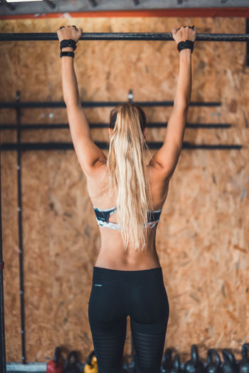 Exercising Indoor Activities Musculation  Squat Blond Hair Blonde Exercising Cross Training Crossfit Crossfit Girl Energy Healthy Lifestyle Kettlebell  Kipping Lifestyles Muscular Build One Person One Young Woman Only Pull Up Real People Rear View Sport Clothing Stretching Training Weightlifting Workout