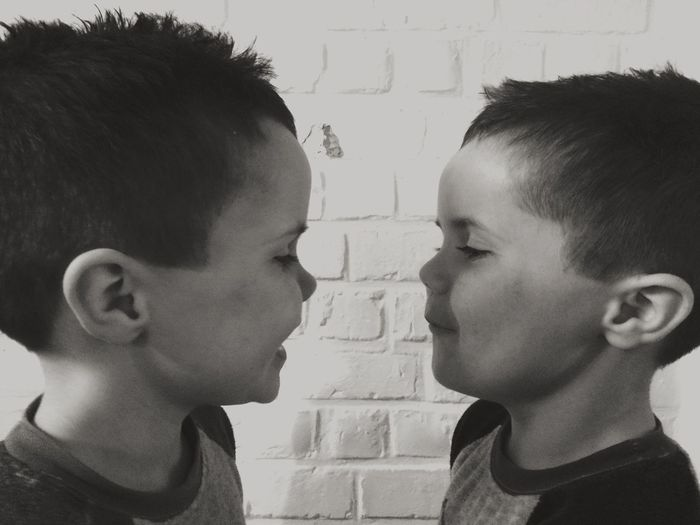 Cute twin brothers standing against brick wall