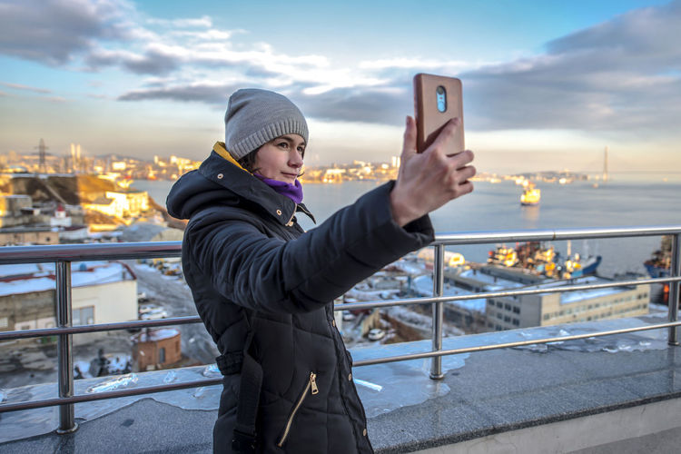 Man photographing while standing in city against sky during winter