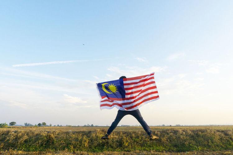 Flag flying over field against sky