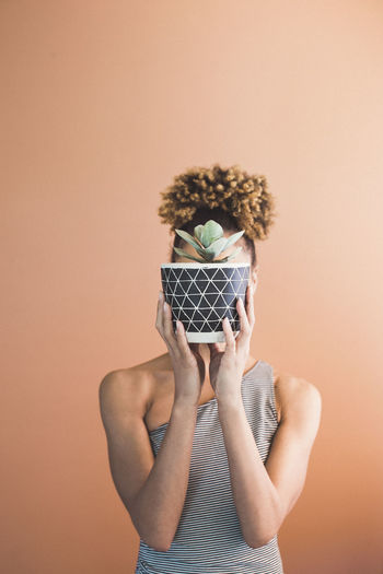 Woman Covering Face With Potted Plants Against Orange Background