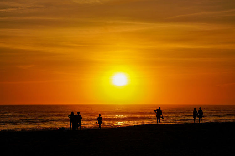 Silhouette people on beach during sunset