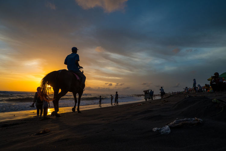 People riding horse on beach against sky during sunset