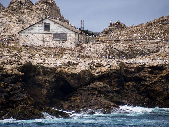 Rocks by sea against buildings