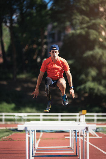 Young Athlete With Prosthetic Leg Jumping Over Railings On Running Track