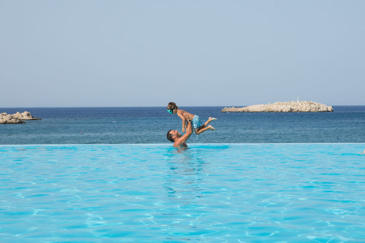 Man carrying son in infinity pool