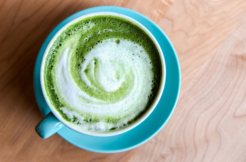 A warm cup of Matcha Latte - from the top - green tea latte with a swirl on a table Caffeine Latte Matcha Matcha Latte Tea Cafe Cup Drink Flat Lay Green Tea Matcha Tea Tea Latte