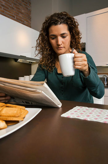 Young woman having breakfast in the kitchen and looking the newspaper Vertical Copy Space Female Girl Technology Comfortable Enjoying Relax Sitting One News Modern Serious Biscuits Indoor Internet Real Curly Hair Surprised Young Concentrated Adult Alone Journal Sunday People Holding Napkin Looking Lifestyle Portrait Caucasian Home Unmarried Worried Kitchen Tranquility Morning Interested Coffee Drinking Newspaper Reading Breakfast Pajama Woman Single