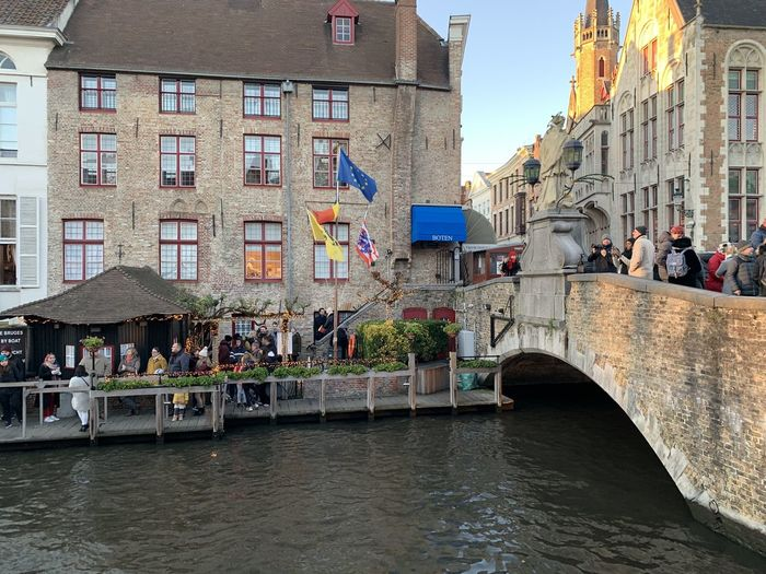 People on bridge over canal amidst buildings in city
