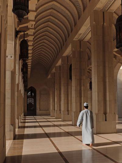 Rear view of man walking in mosque corridor