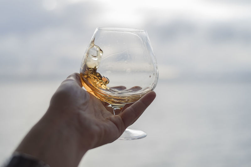 Swirling a snifter of whiskey by the sea Adults Only Alcohol Beverage Brandy Close-up Cloud - Sky Crystal Ball Day Dram Drink Drinking Glass Focus On Foreground Glass - Material Holding Human Body Part Human Hand Nature Outdoors People Refreshment Sky Snifter Water Whiskey Wineglass