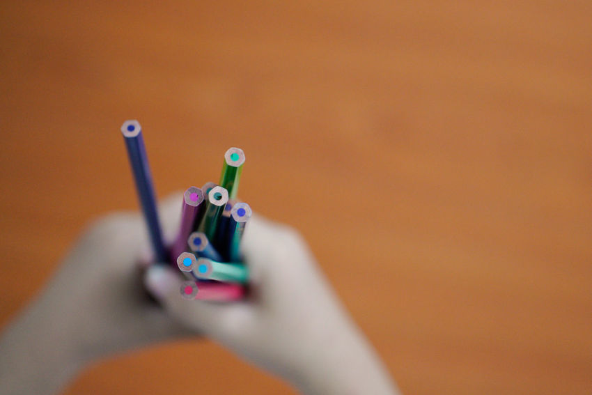 A children hand holding a bunch of colourful pencil Back To School Close-up Colorful Day Indoors  Multi Colored No People Pencil Pencil Art Straight Pin