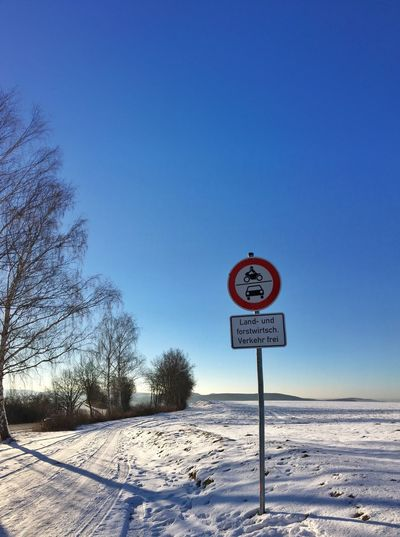 Metallic Sign By Snow Covered Road Against Clear Blue Sky