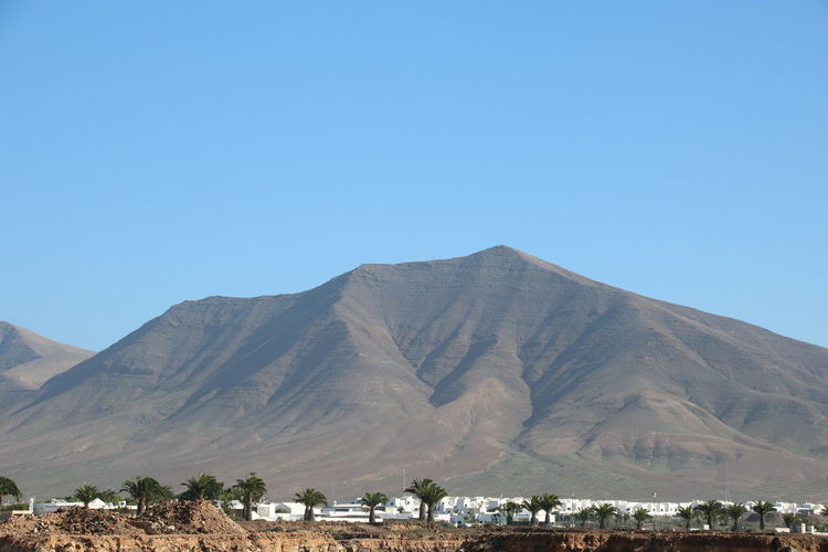 Mountain Sky Scenics - Nature Landscape Clear Sky Copy Space Beauty In Nature Land Nature Environment Tranquil Scene Tranquility Blue Built Structure No People Mountain Range Day Travel Destinations Non-urban Scene Outdoors Climate Arid Climate Extinct Volcano Playa Blanca Lanzarote