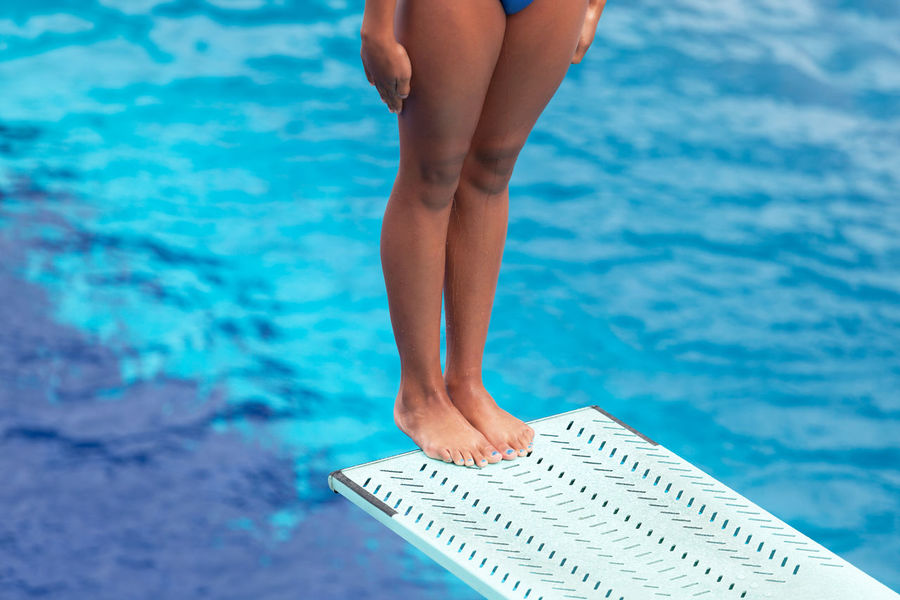 Female diver standing on a springboard, preparing to dive Diving Jump Standing Swimming Woman Board Concentrate Concentration Concept Dive Diver Diving Board Feet Female Girl Legs Pool Preparation  Sport Springboard Springboard Diver Summer Swimming Pool Unrecognizable Person Water