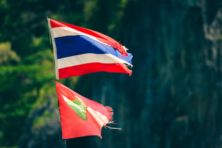 Thai flag with mountains in the bakground, Phi Phi Leh, Thailand. Thai Thailand Beach Day Flag Focus On Foreground National Icon Nature No People Outdoors Patriotism Phi Phi Island Pole Pride Red Striped Waving Wind