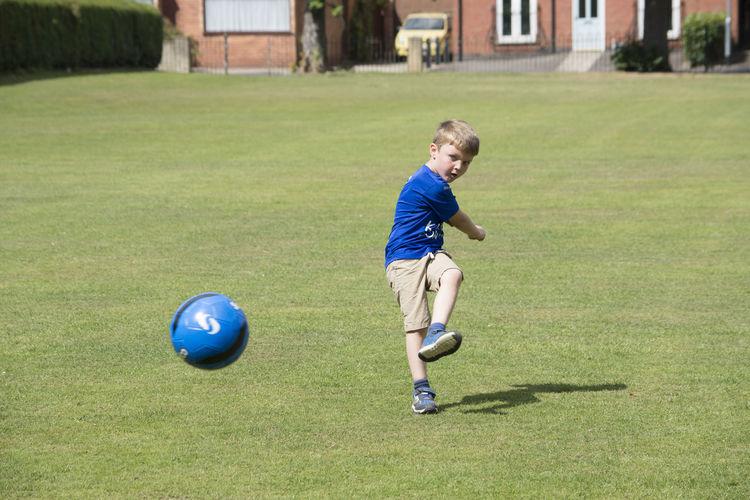Boy Kicking Soccer Ball On Grassy Field