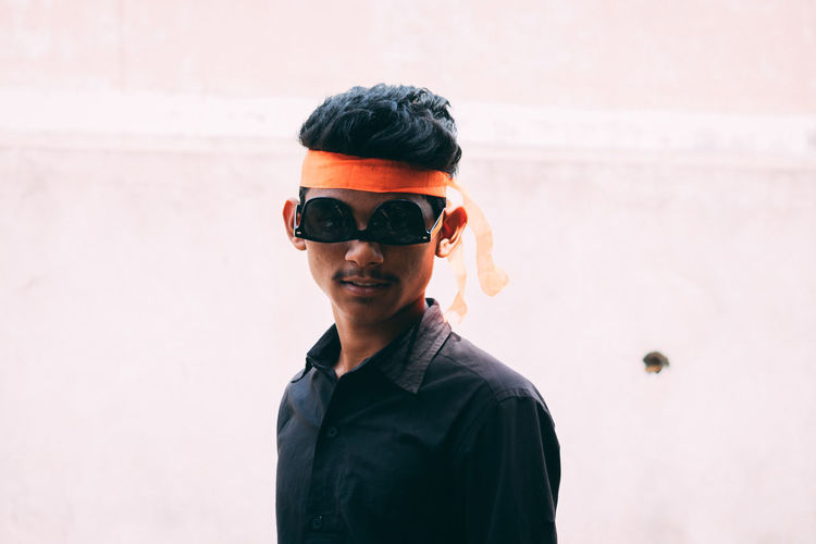 Portrait of young man wearing sunglasses upside down standing outdoors