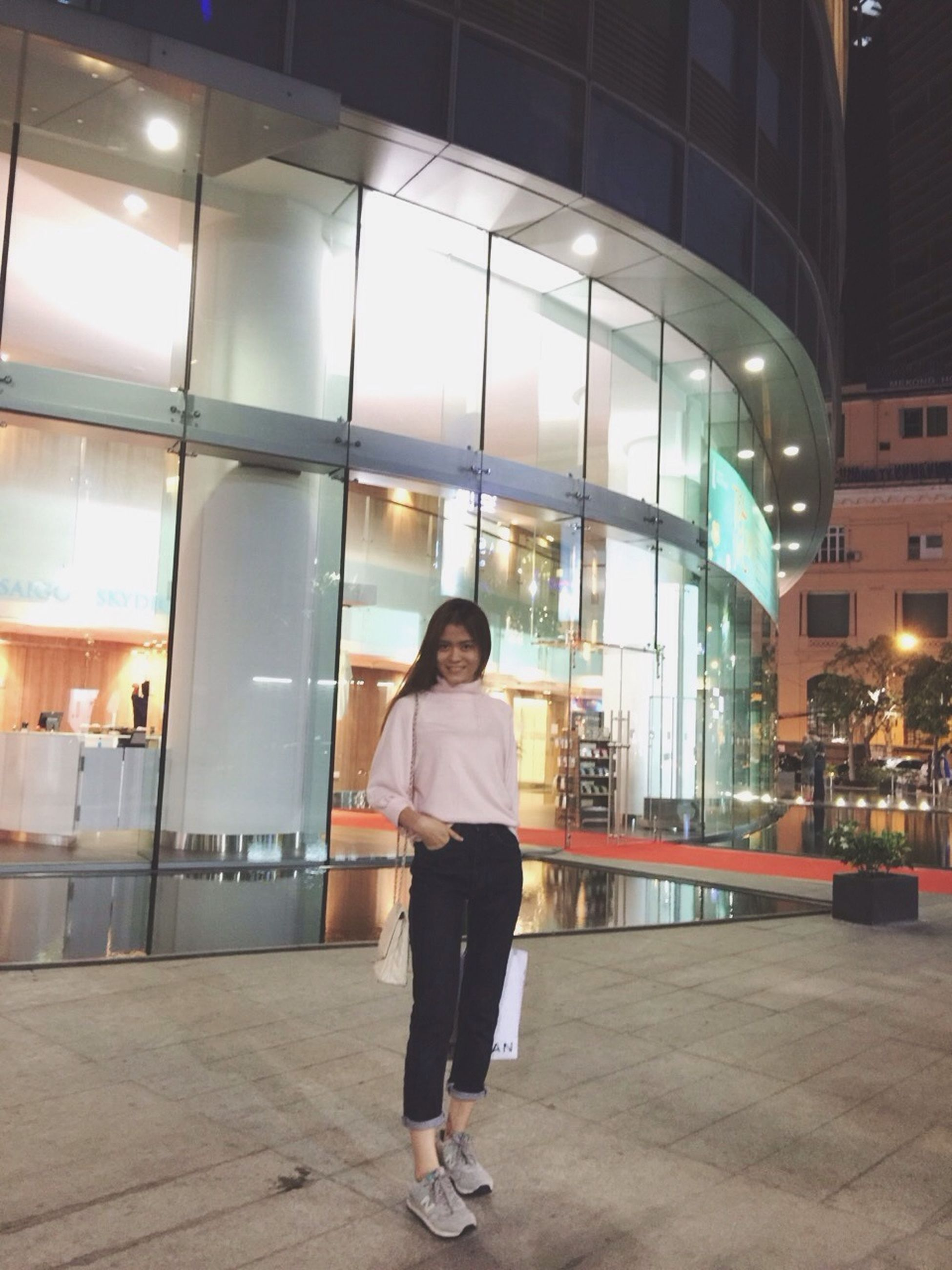 full length, architecture, lifestyles, built structure, casual clothing, standing, illuminated, building exterior, leisure activity, indoors, walking, city, rear view, night, reflection, city life, person, building