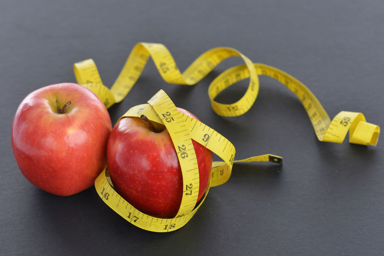 An apple with measuring rope Apple - Fruit Close-up Day Freshness Fruit Healthy Eating Healthy Lifestyle Indoors  Large Group Of Objects Measuring Rope Measuring Tape No People Studio Shot Text Variation