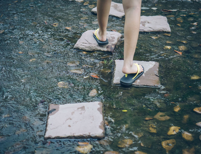 The girl's leg is crossing the middle of the stream. Travel Footpath Walking Nature Human Foot Water Outdoors Shoe