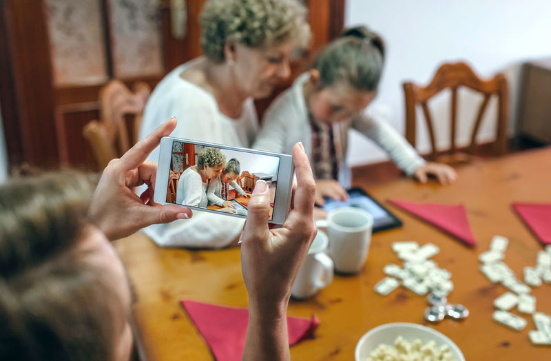 Woman photographing daughter with grandmother from mobile phone at home