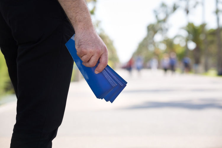 Midsection of man holding envelop on road against sky