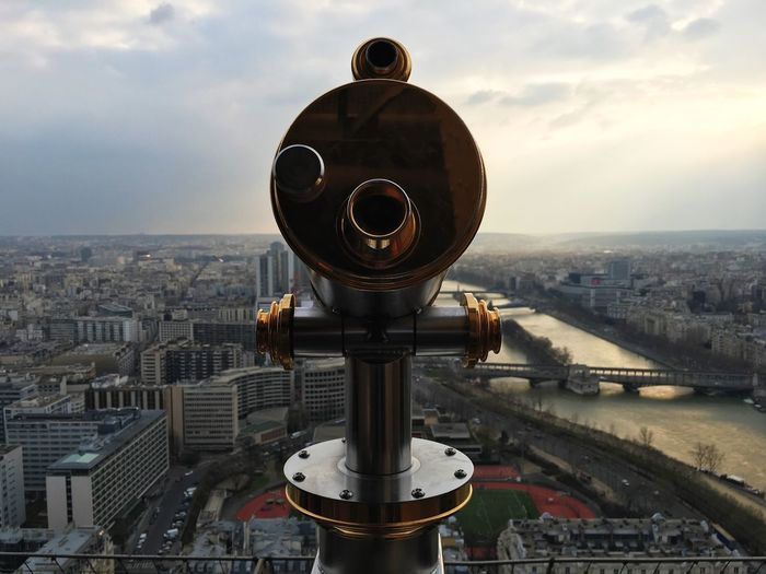 Coin-Operated Binoculars In Front Of Seine River And Buildings In City At Sunset