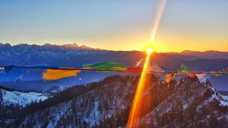 Colorful Prayer Flags Waving Against Snowcapped Mountains During Sunset