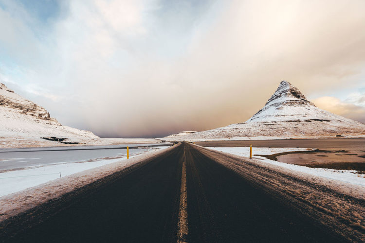 Kirkjufell mountain in Iceland Beauty In Nature Cold Temperature Day Landscape Mountain Nature No People Outdoors Road Scenics Sky Snow The Way Forward Tranquil Scene Tranquility Transportation Weather Winter