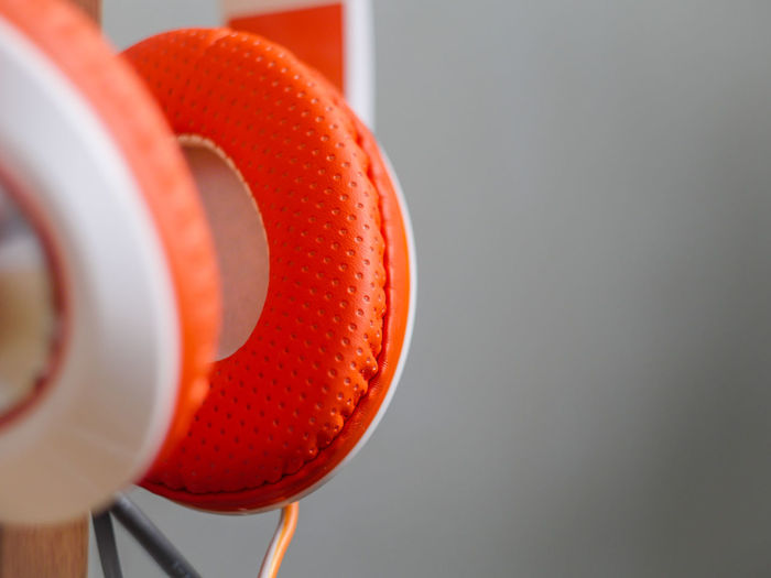 Close up focus on orange headphone that hang on wall. New product design for children and teenager. One of popular accessories of new young generation. Headphones Modern Young Accessories Arts Culture And Entertainment Close-up Copy Space Design Equipment Focus On Foreground Generations Headset Indoors  Input Device Microphone Music No People Orange Color Red Selective Focus Still Life Studio Shot Style Technology Teenager
