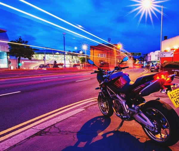 City Street City City Life Transportation Outdoors Illuminated Nightlife Cityscape Mode Of Transport Aprilia Shiver Longexposurephotography Lighttrials Bicycle Street Cycling Traffic Night Blurred Motion Sky Motorcycle Cloud - Sky Road Red