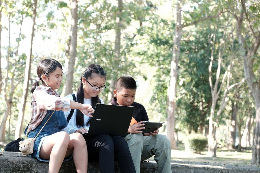 Bench Child Childhood Communication Day Digital Native Digital Tablet E-mail Education Friendship Holding Internet Learning Looking Down Males  Nature Outdoors People Reading Sitting Student Technology Togetherness Using Computer Wireless Technology
