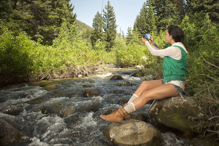 Woman Photographing With Smart Phone While Sitting On Rocks By River
