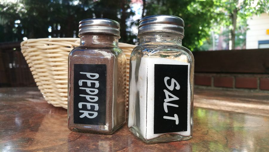 Text on pepper and salt shaker at table