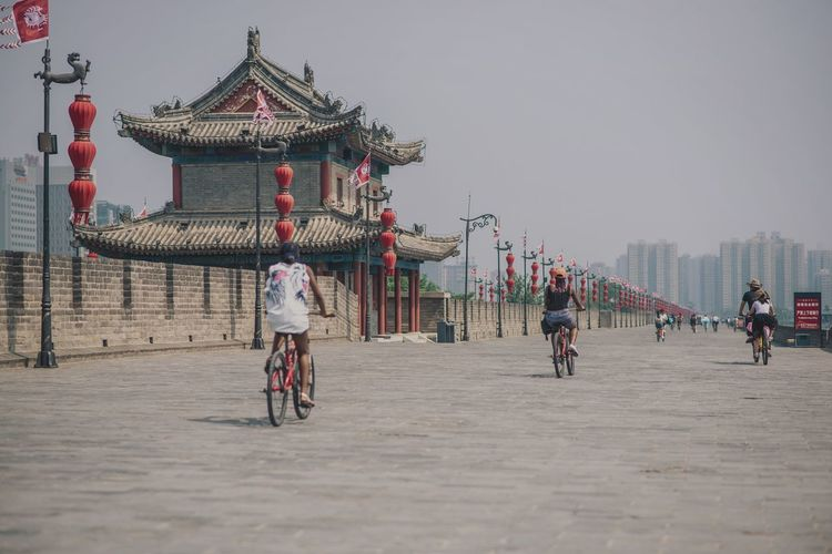 People riding bicycle by drum tower in xi an against sky