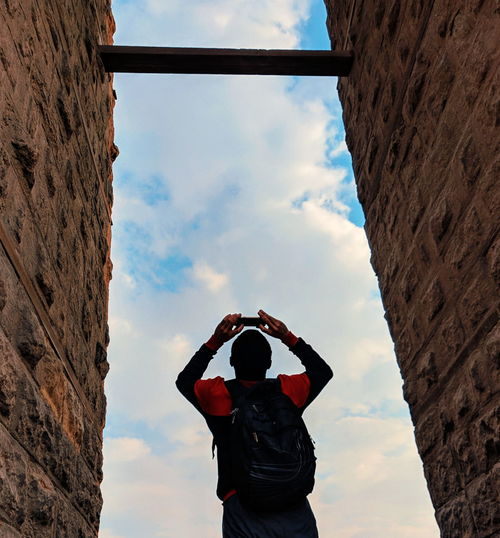 Rear view of man photographing by stone wall against cloudy sky
