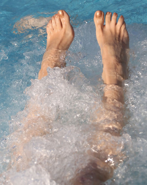 two feet of barefoot woman on the spa resort Therapy Activity barefoot Beauty Care Girl Human Body Part Human Leg Hydromassage Hydrotherapy Hydrothermal Leisure Activity Lifestyles Massage One Person Outdoors Pool Real People Skin Care Skincare Spa Splashing Swimming Pool Water Wet